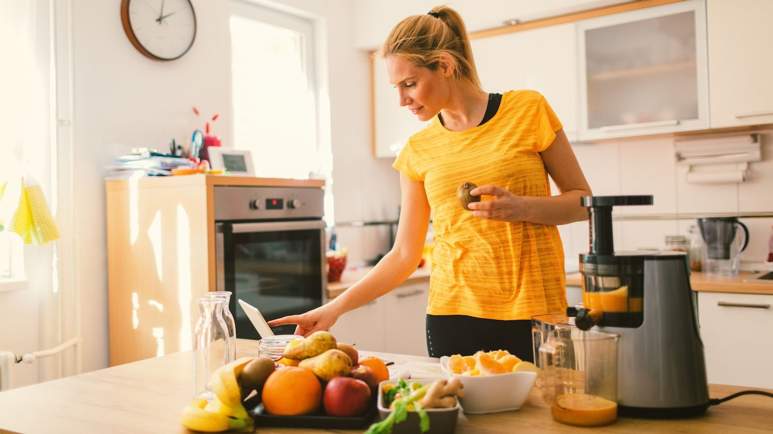 Woman using a juicer in her kitchen while looking at a recipe on her laptop
