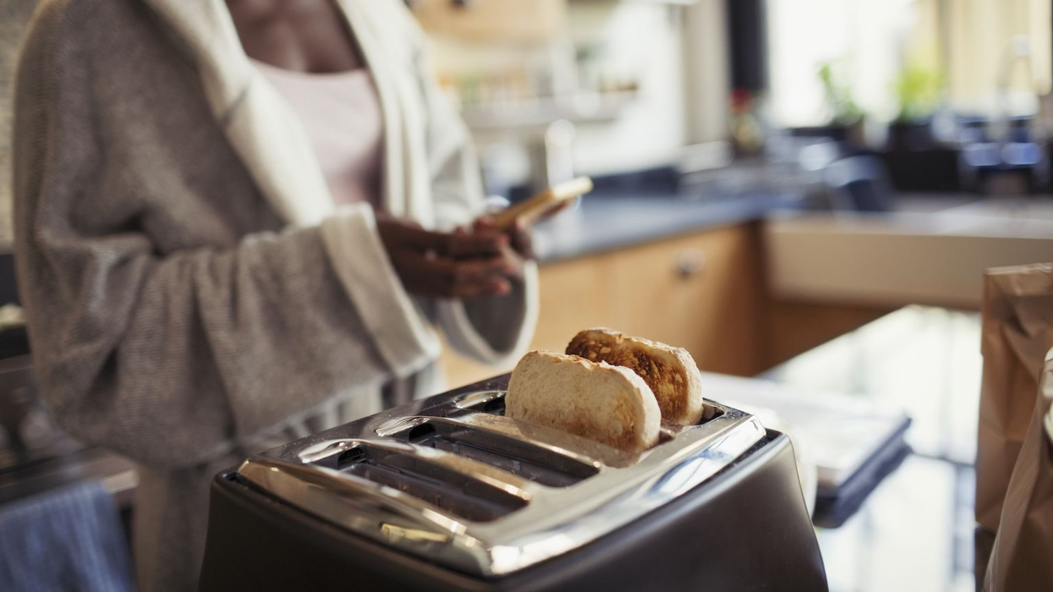 Close up of a woman toasting bread in a toaster while using her mobile phone.