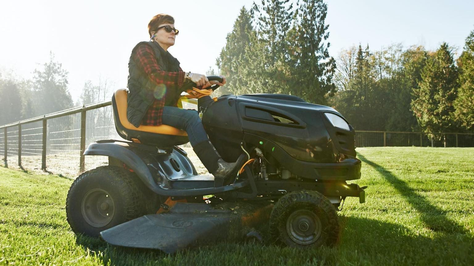 Shot of a mature woman driving a lawnmower on a farm