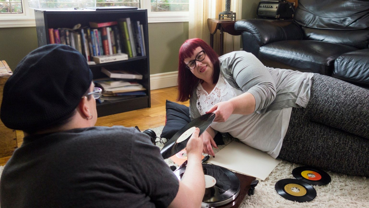 Plus size woman and her husband listening to records on their living room floor.