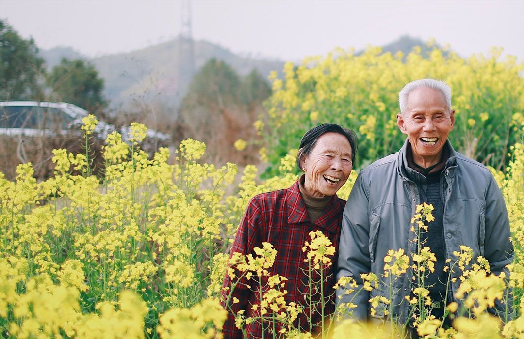Elderly couple in field smiling