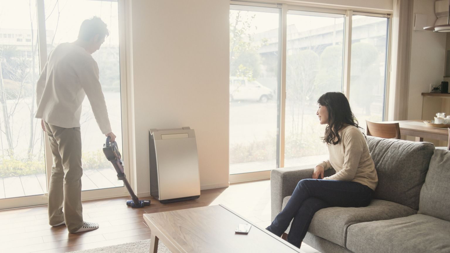 Man vacuuming in his living room while a woman watches from the couch