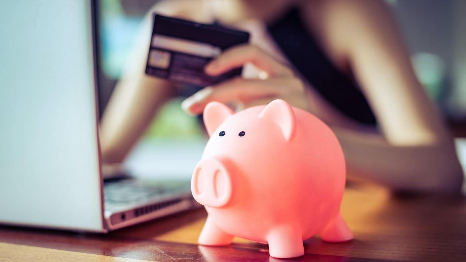 A piggy bank sitting in front of a woman who is holding a credit card and looking at a laptop.