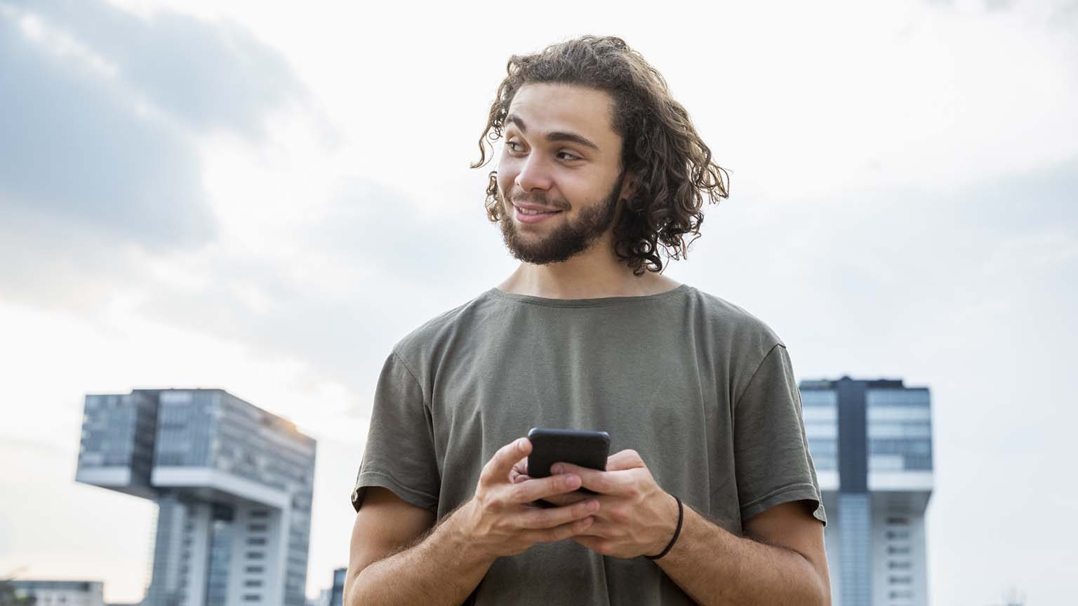 Germany, Cologne, smiling young man holding cell phone looking sideways