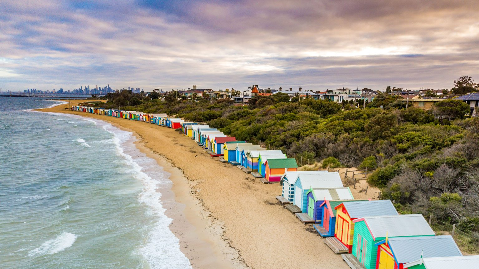 Drone view of Brighton Bathing Boxes in Victoria with cloudy sky in the background, Australia