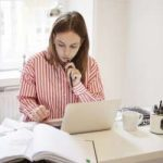 Female accountant using laptop while doing paperwork at home