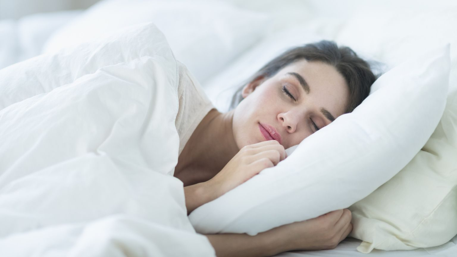 Woman sleeping comfortably on soft white pillows
