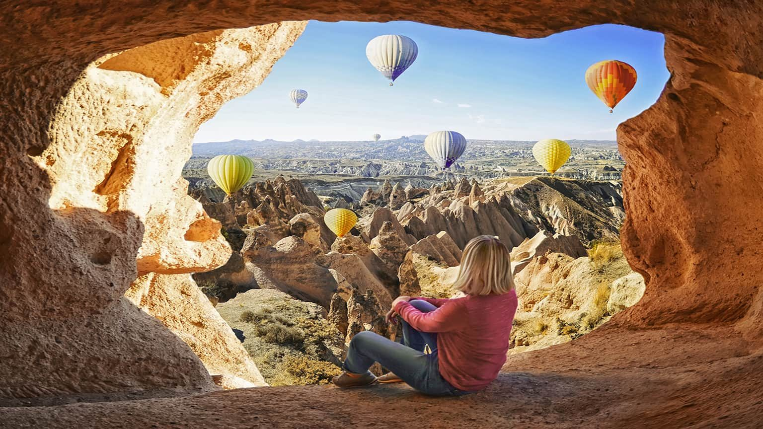 Woman watching colorful hot air balloons flying over the valley at Cappadocia, Turkey