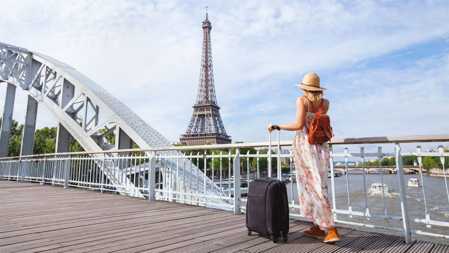 Woman with suitcase near Eiffel Tower, France