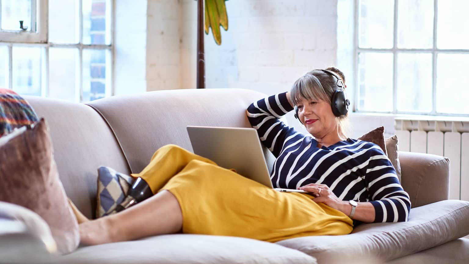 Woman with white hair wearing Bluetooth headphones and relaxing on a couch
