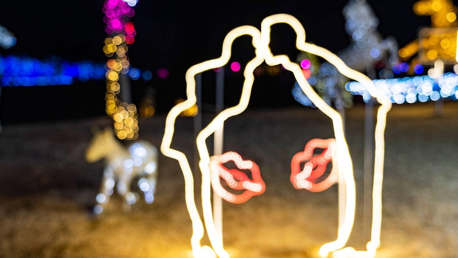 Christmas lights, couple kissing.
