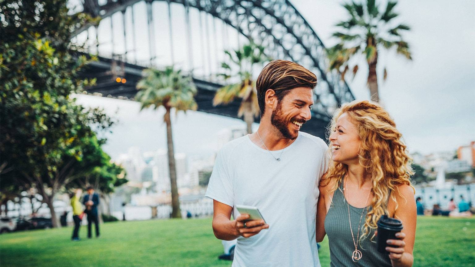 Smiling couple in front of the Sydney Harbour Bridge