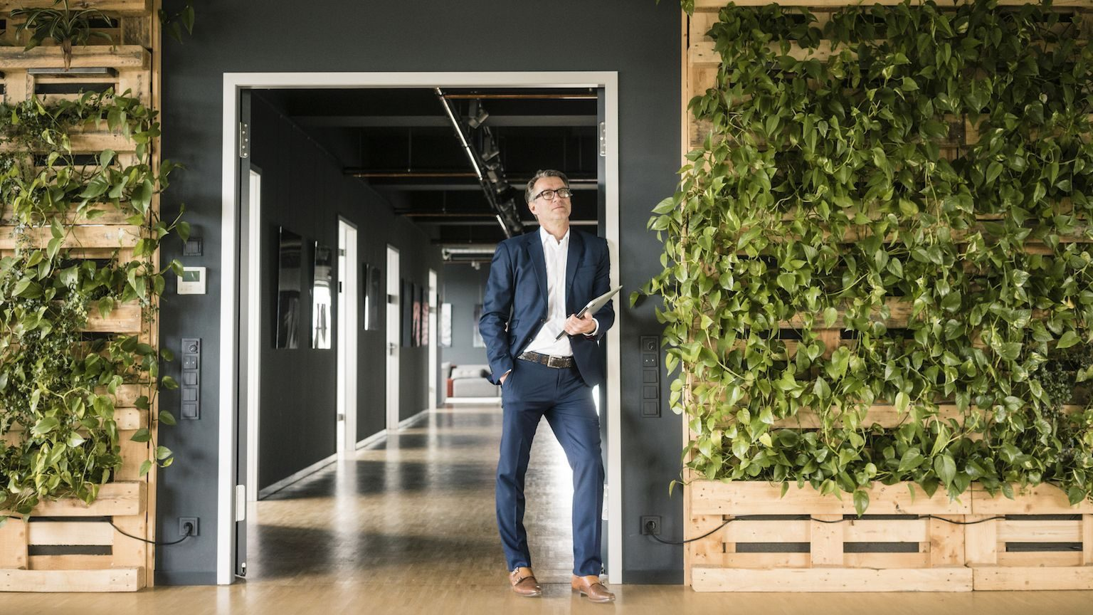 A man in a suit standing in front of a wall covered with hanging plants