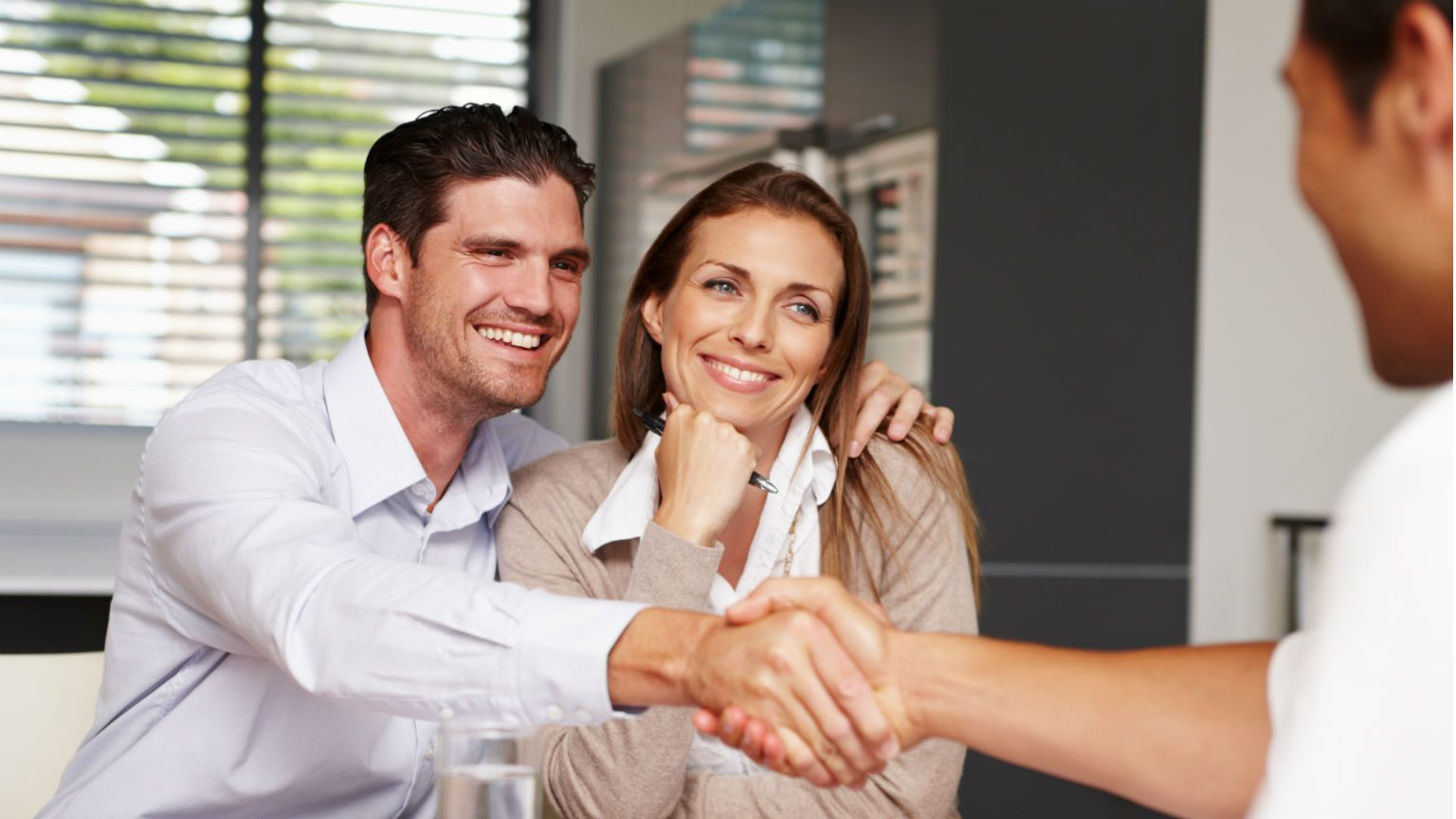 Happy couple shaking hands with financial advisor.