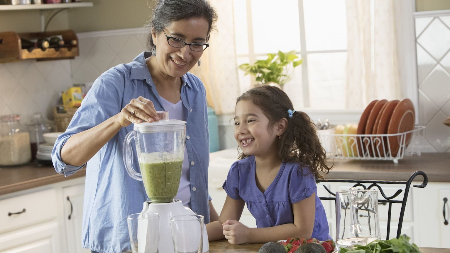 Grandmother and granddaughter making a green smoothie in a blender.
