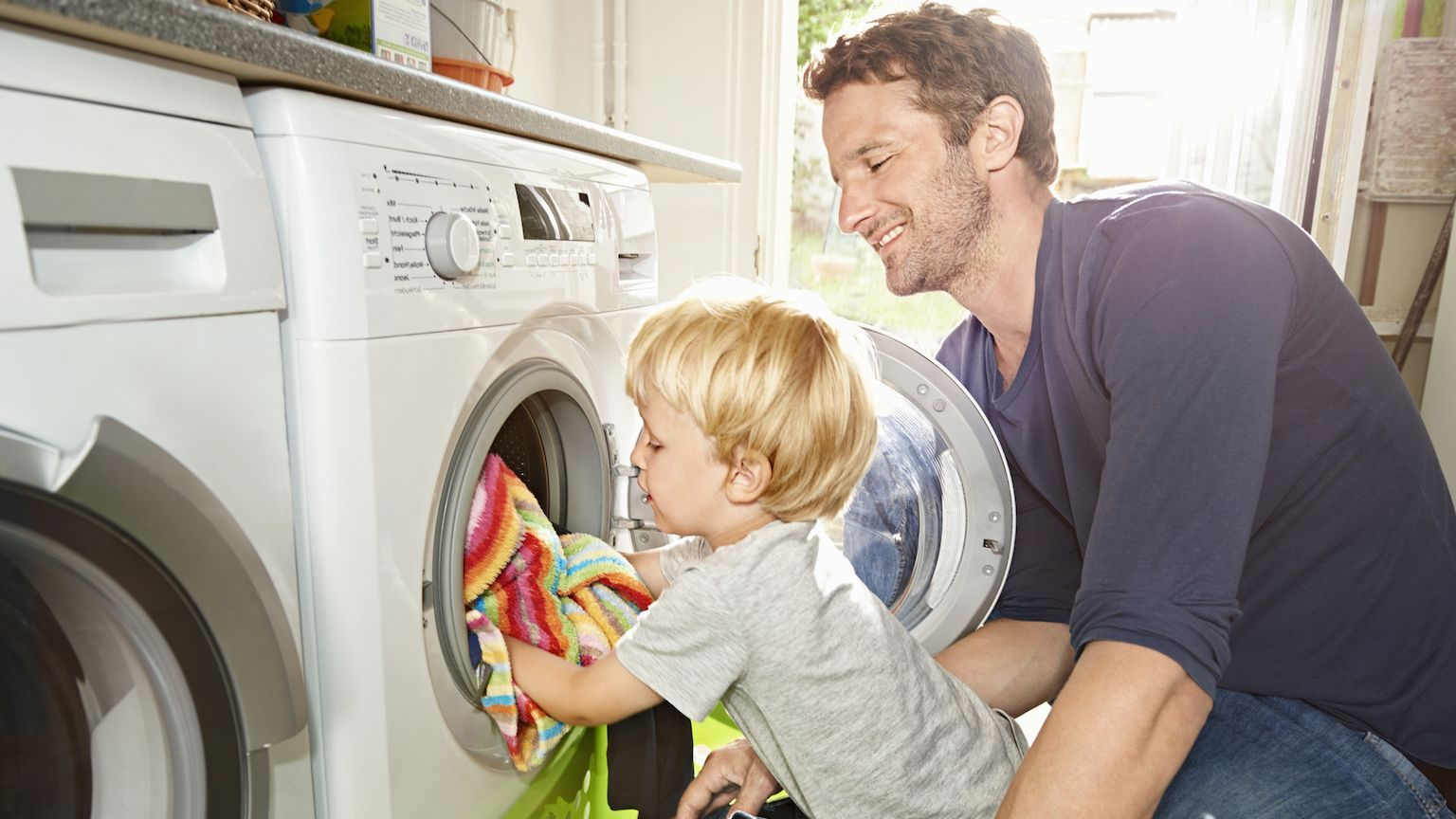 A man and his young son putting towels in their washing machine.