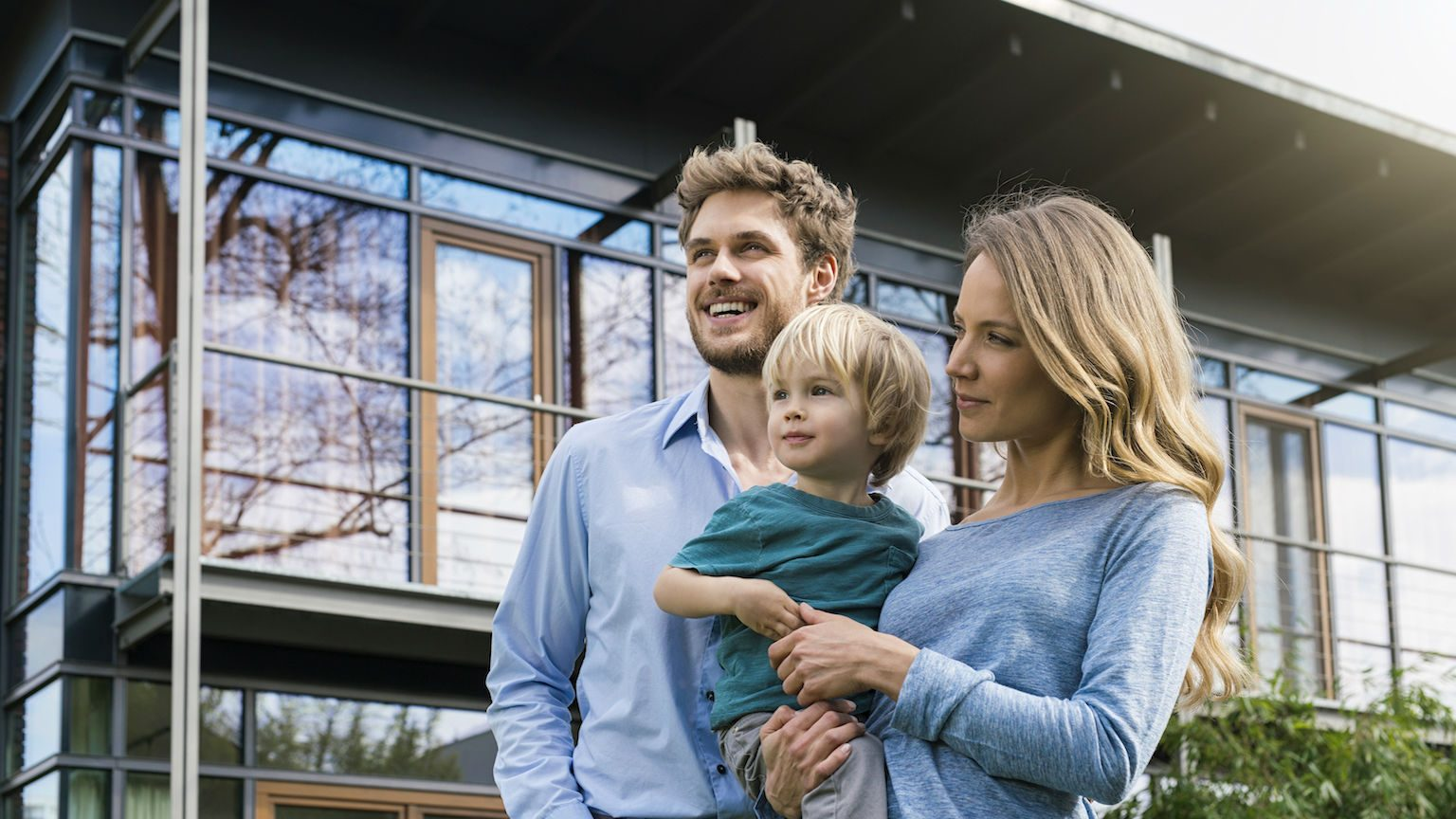 Happy couple with son in front of their home