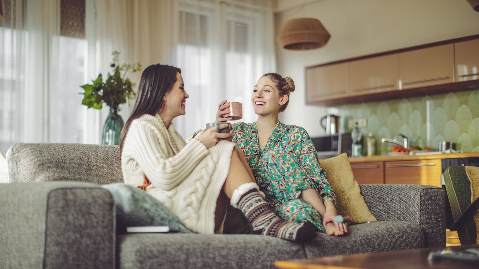 Two women sitting on a couch in warm clothing drinking coffee