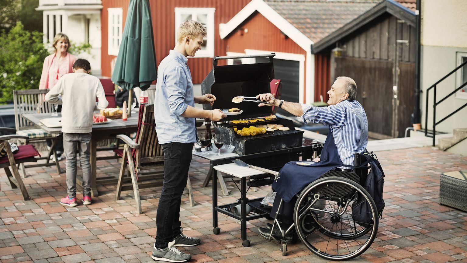 A man in a wheelchair grilling food for his family on a  gas BBQ