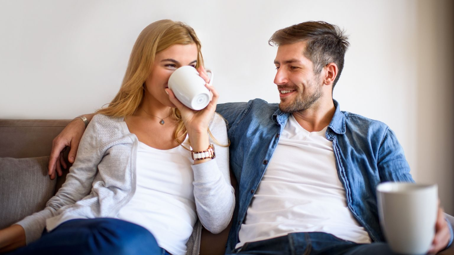Man and woman drinking coffee on a couch in their living room