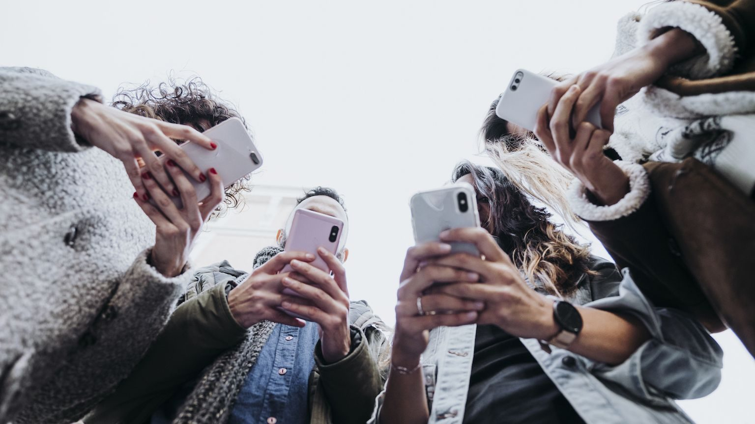 A group of young people holding up their smartphones