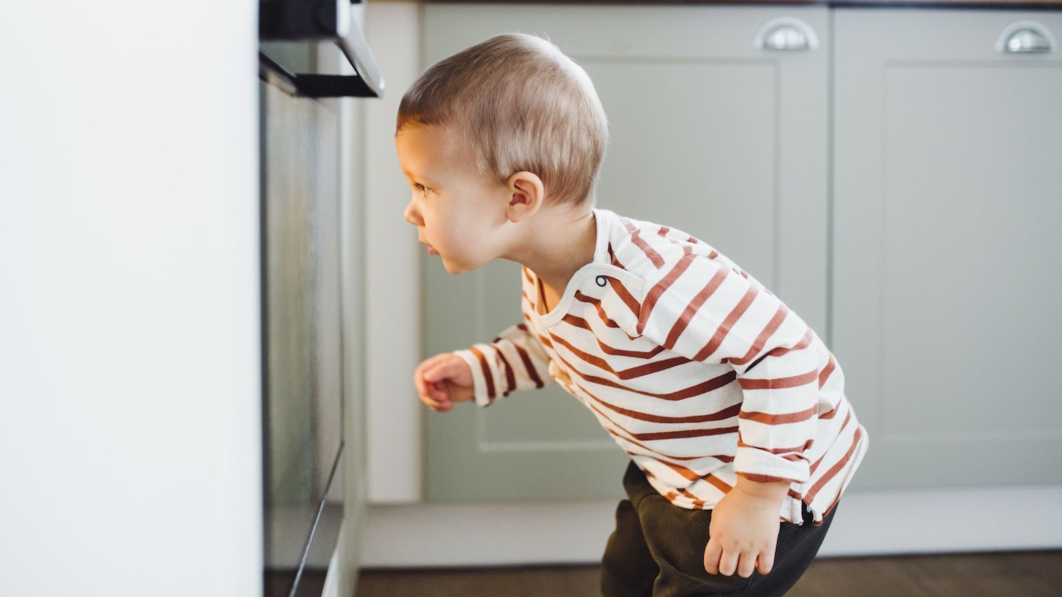Little boy peering into an oven