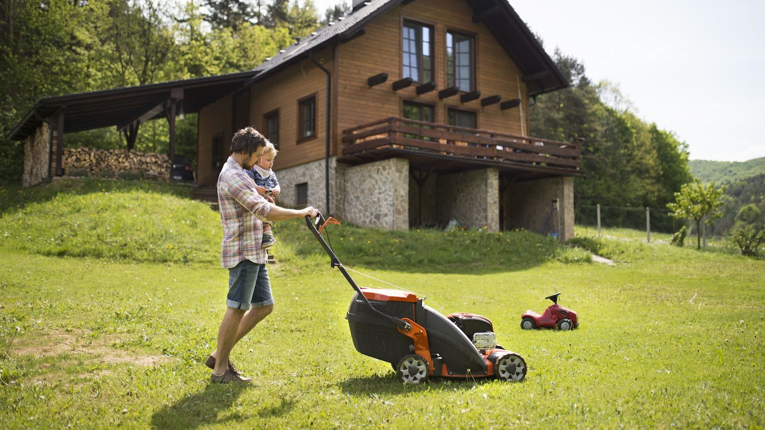 Man moving the lawn while holding his son.