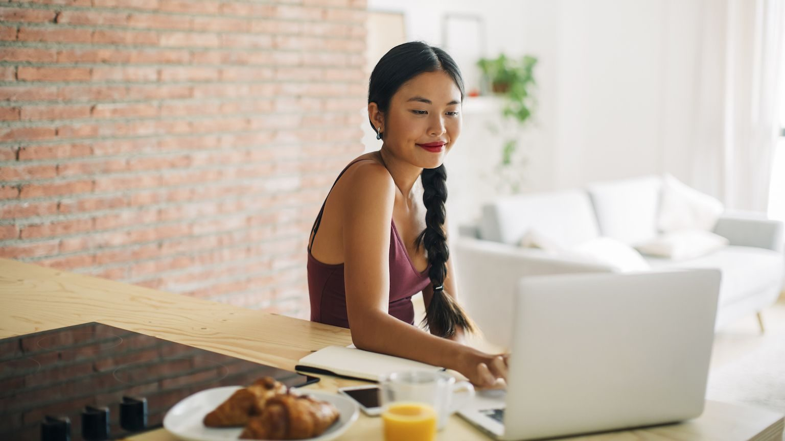 A young woman using her laptop and eating breakfast at home