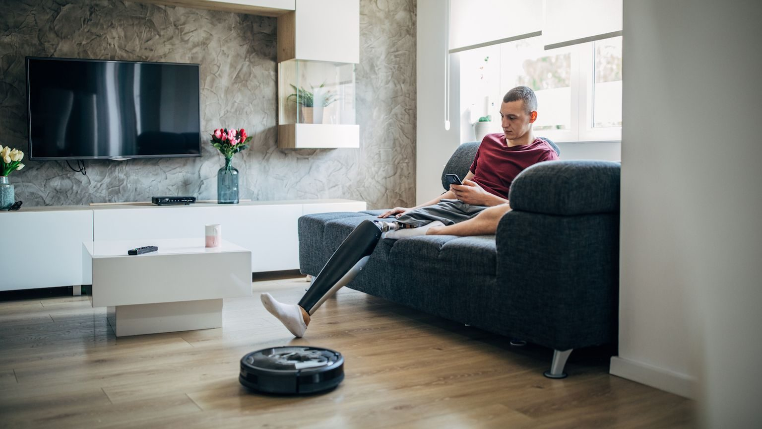 A man with a prosthetic leg using a robot vacuum.