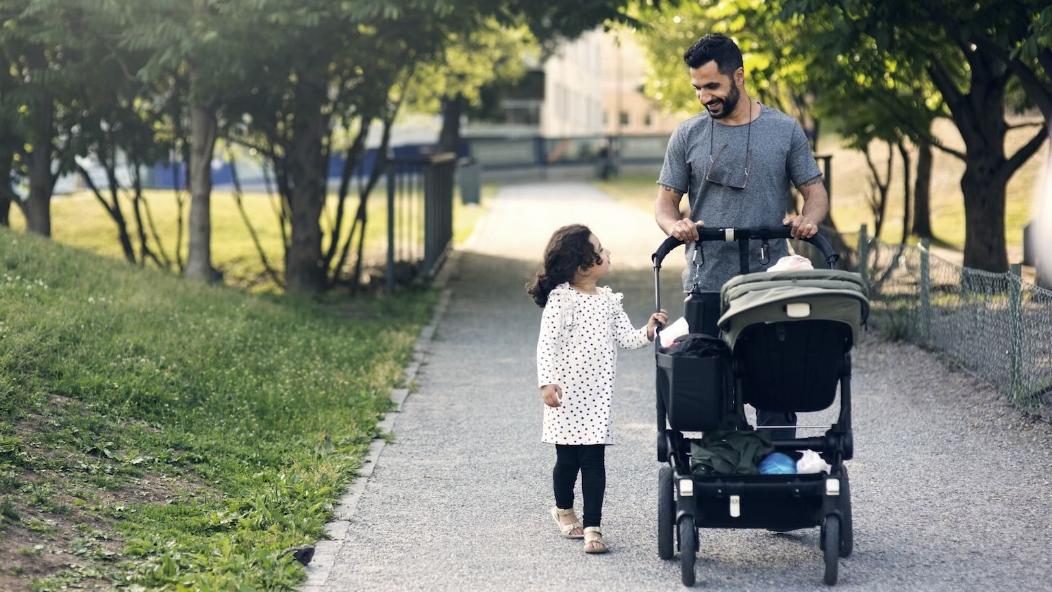 A dad pushing his baby in a stroller while he walks next to his daughter