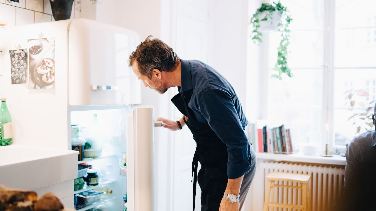 Man looking into the open door of a top mount fridge