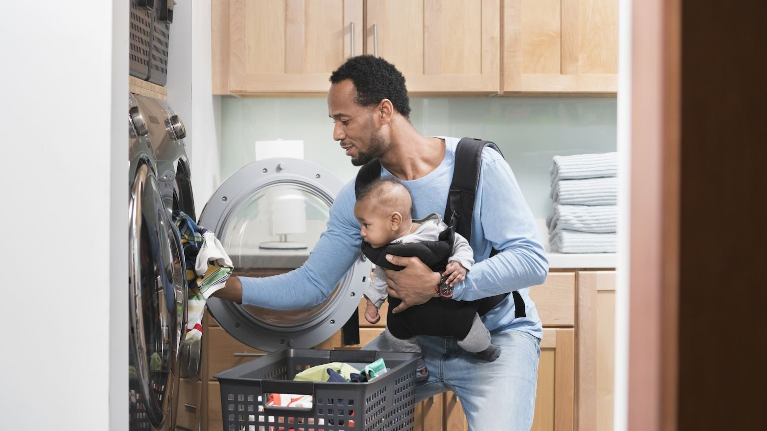Man putting his clothes in the dryer while wearing his baby in a carrier on his chest.