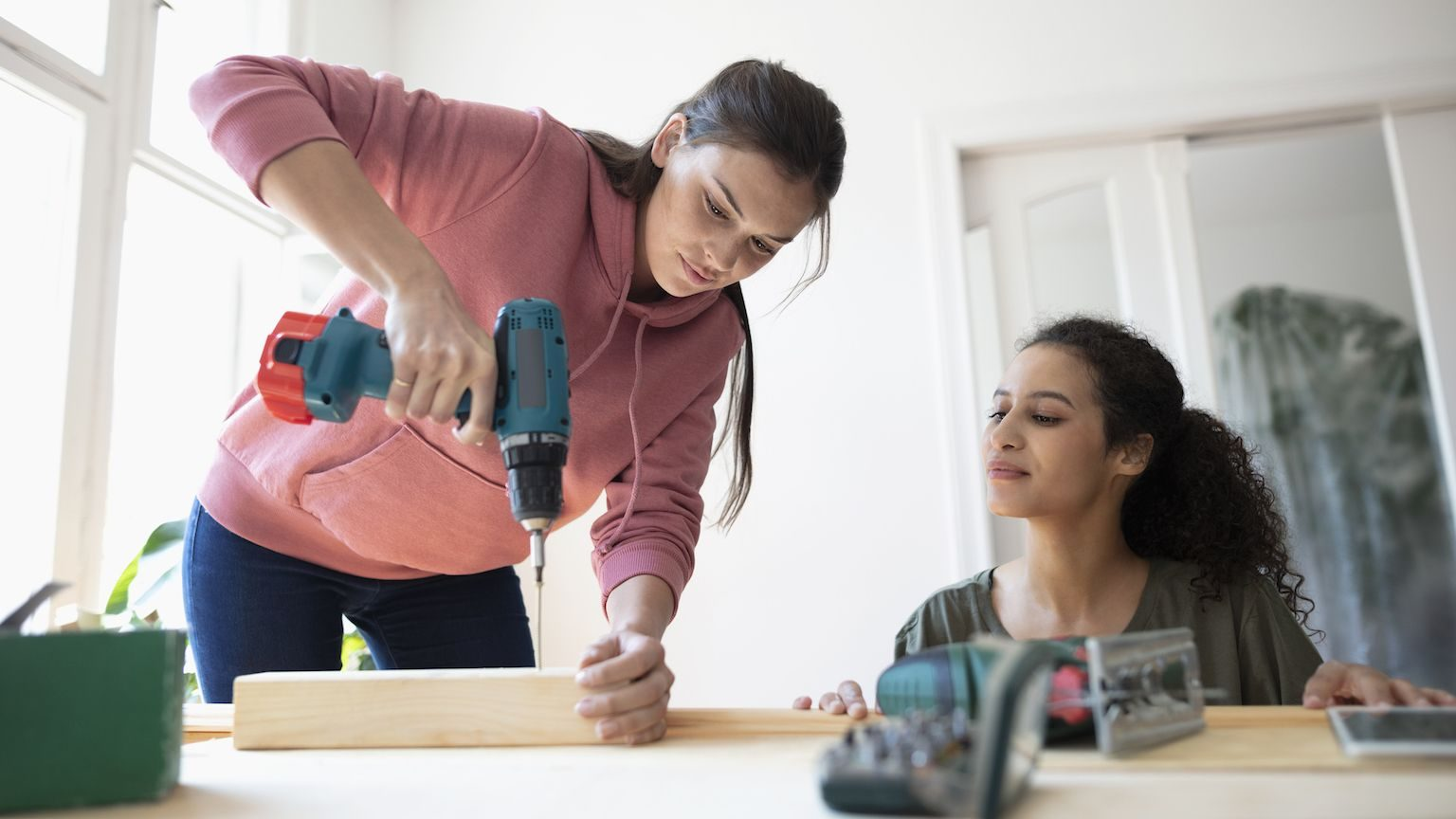 Two women using a cordless drill for a home construction project