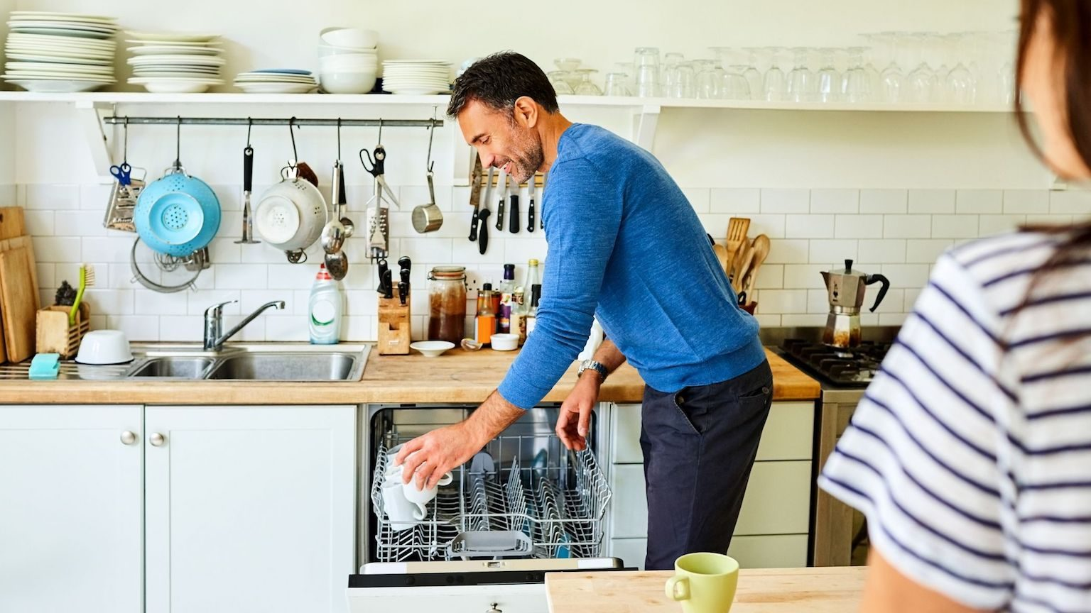 A man loading a dishwasher in his kitchen.