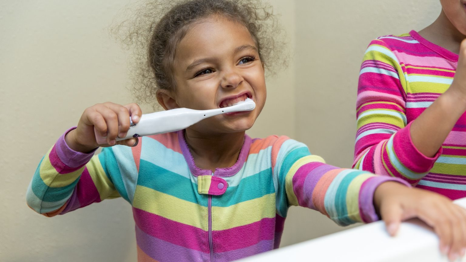 A little girl in bright pyjamas brushing her teeth in front of a mirror
