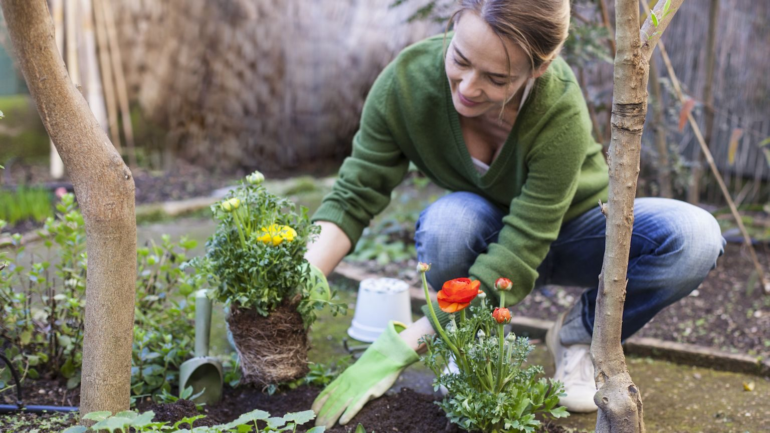 Woman planting flowers in her gardening using gardening tools