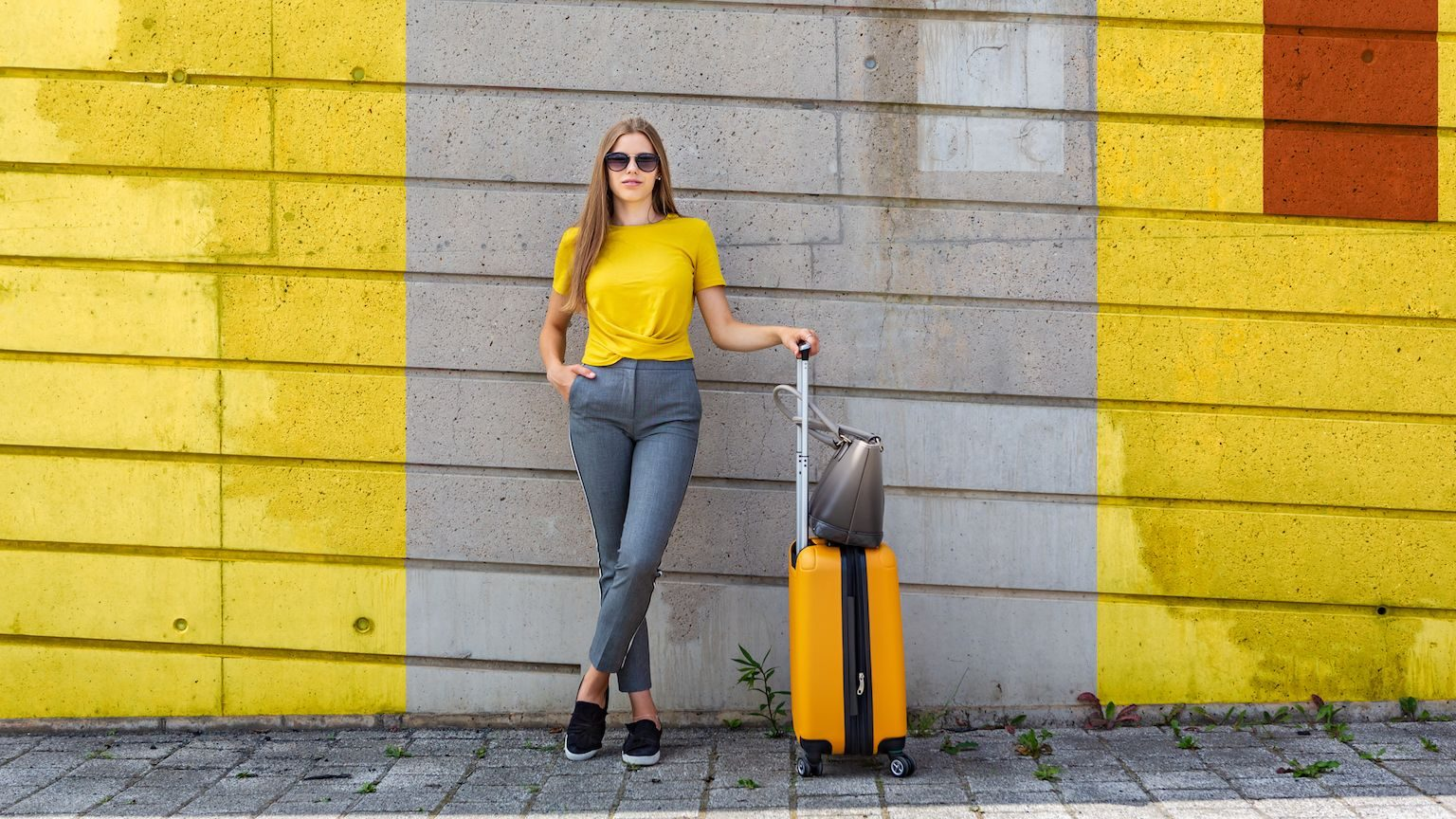 Woman wearing a yellow t-shirt standing with a yellow suitcase in front of a yellow painted wall