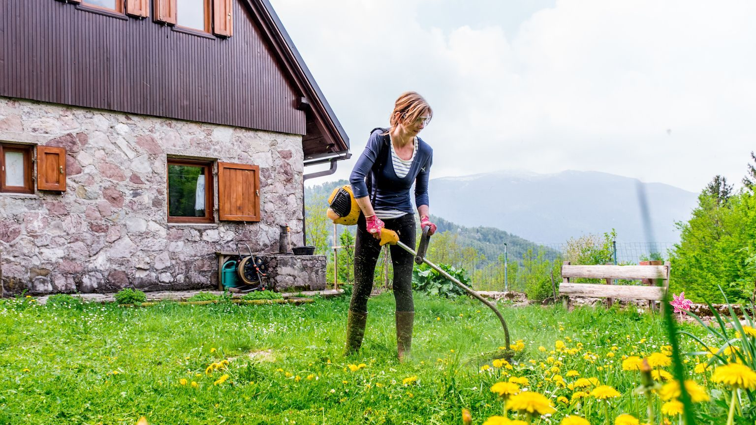 Woman using a whipper snipper to trim the grass outside her house