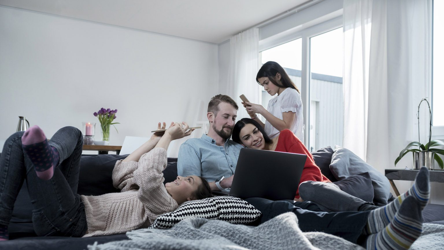 family with gadgets in living room