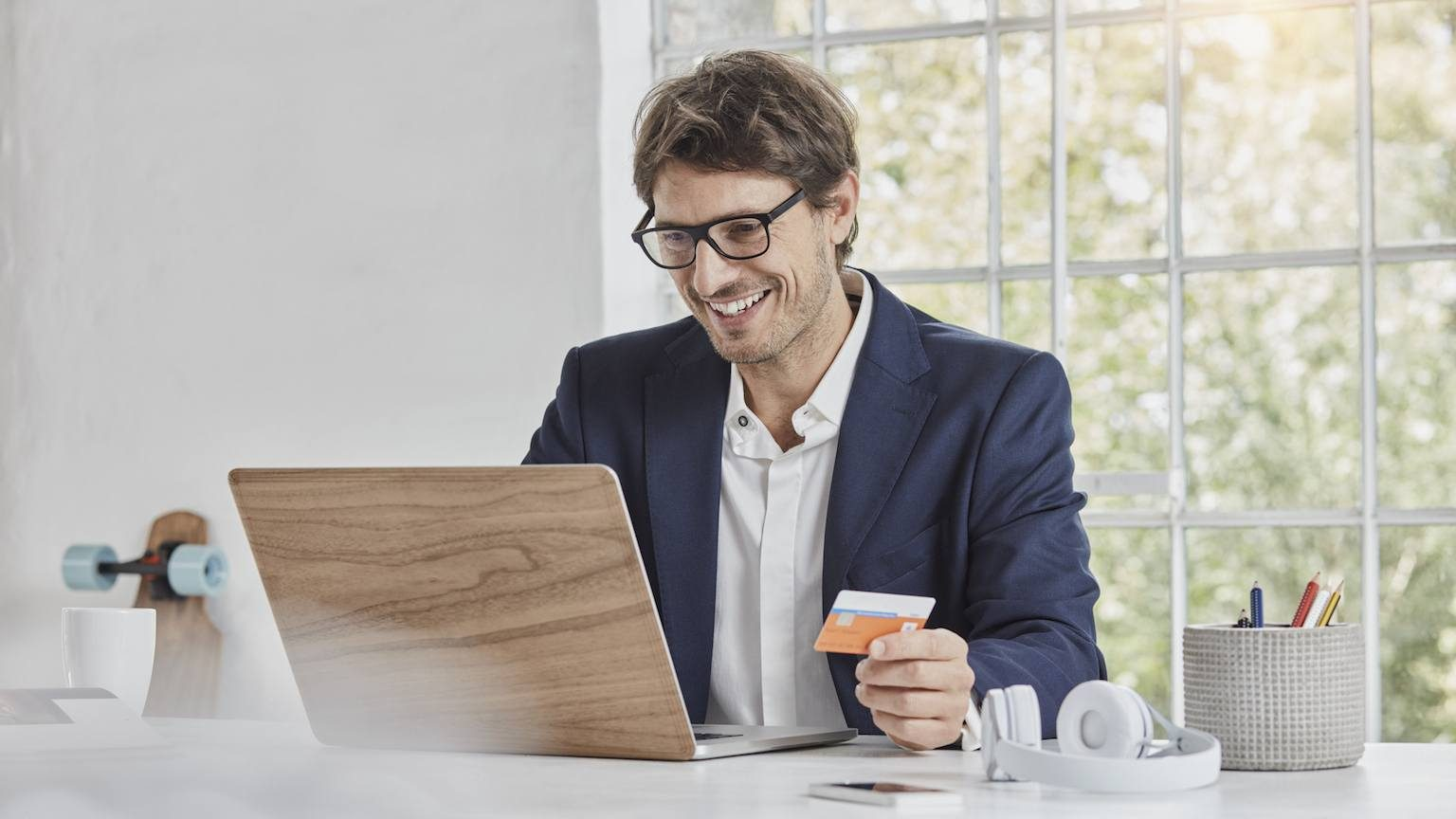 Man holding credit card and looking at laptop in office.