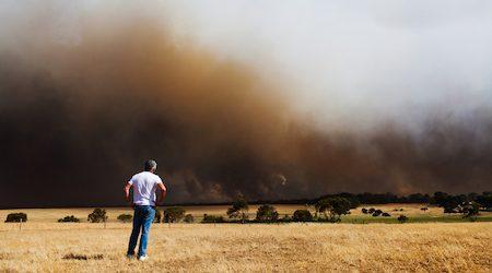 Man watching a bush fire burn