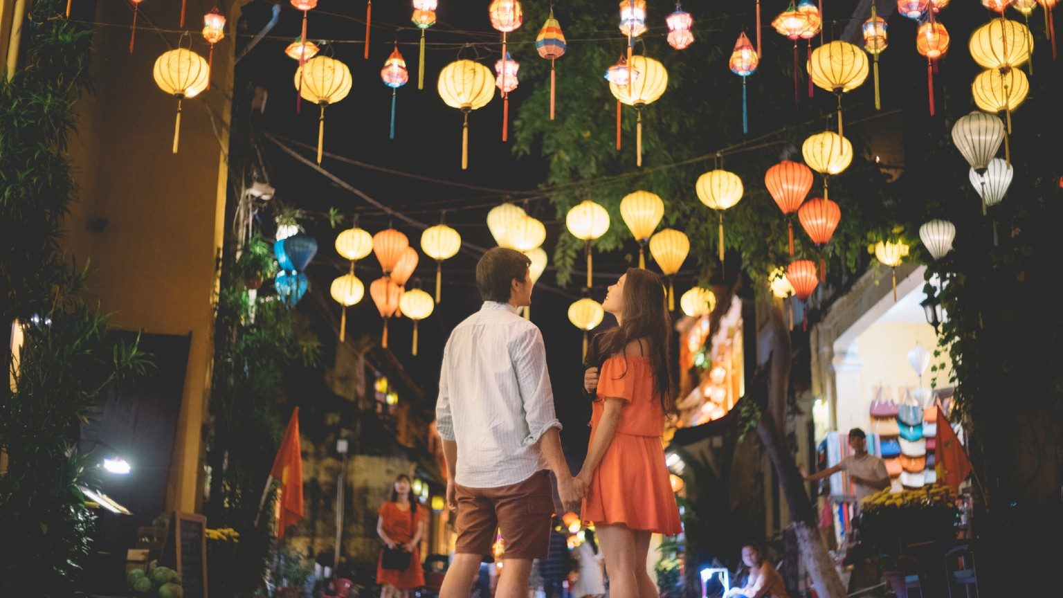 Hoi An couple standing under lanterns.