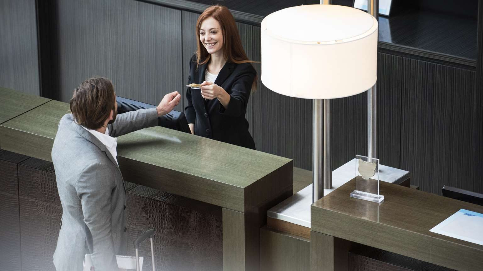 Smiling female receptionist giving credit card to businessman while standing at hotel reception