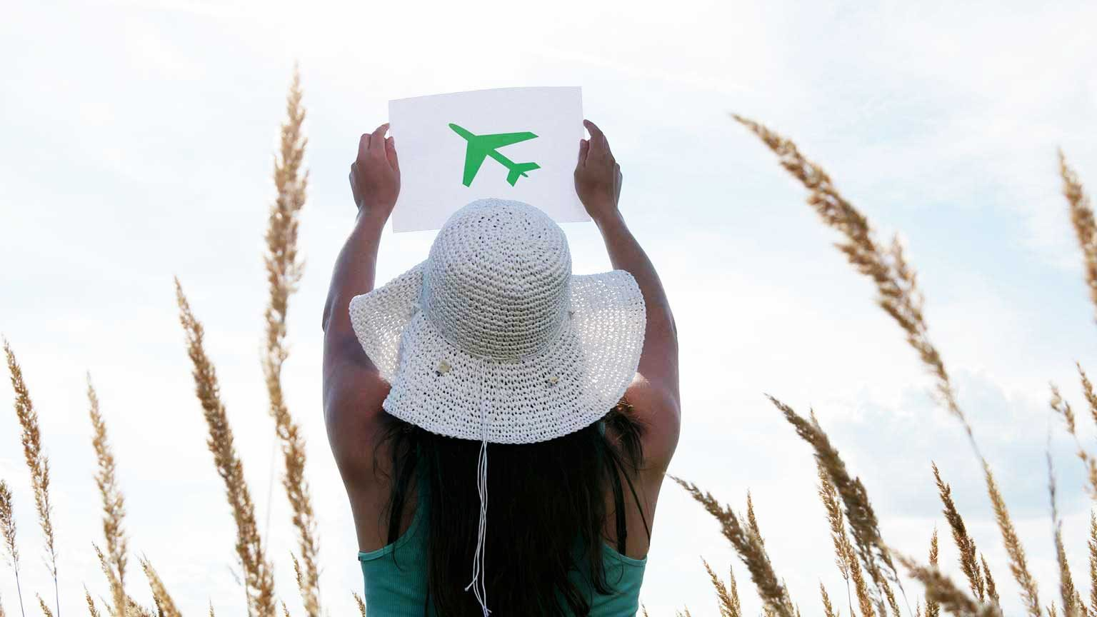 Woman holding a picture of a green airplane.