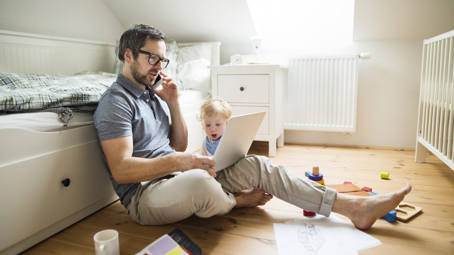 Father with baby looking at laptop and on the phone.