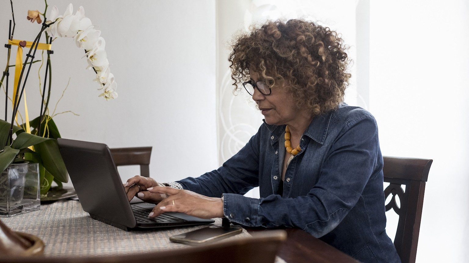 Woman typing on laptop at home.