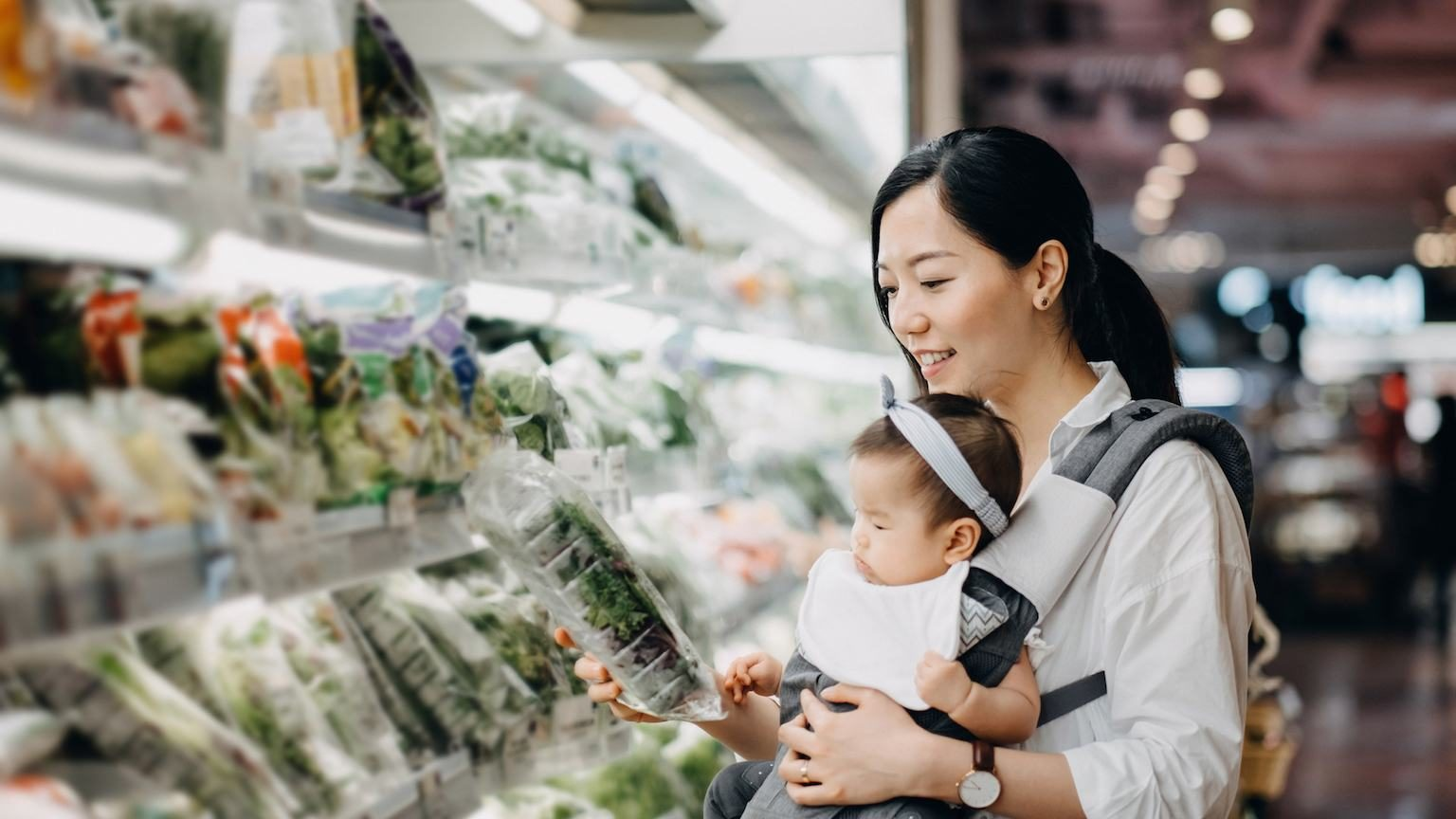 Mum holding baby while shopping for fresh produce in supermarket.