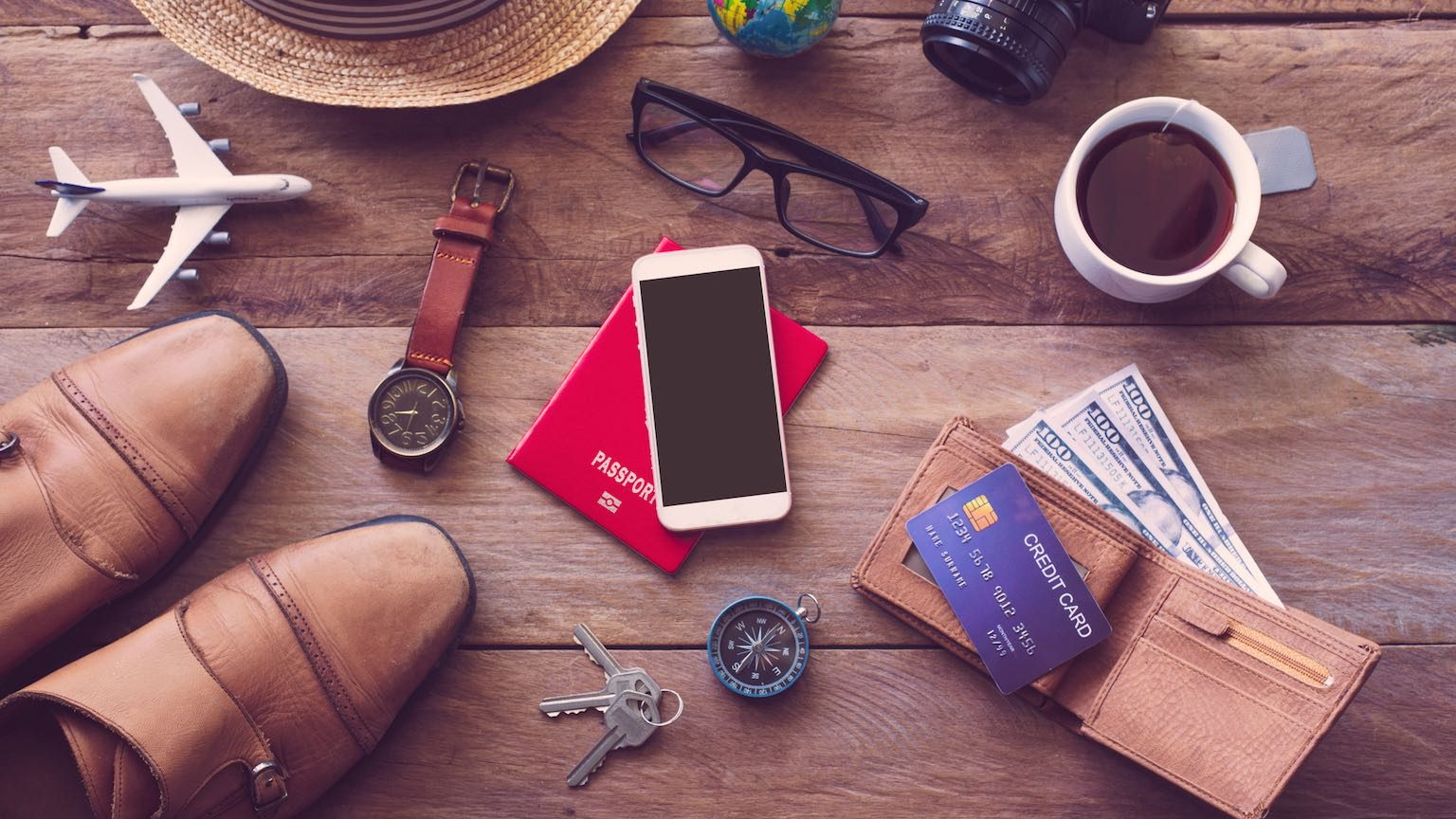 Flat lay of travel essentials including credit card, cash, passport and glasses.