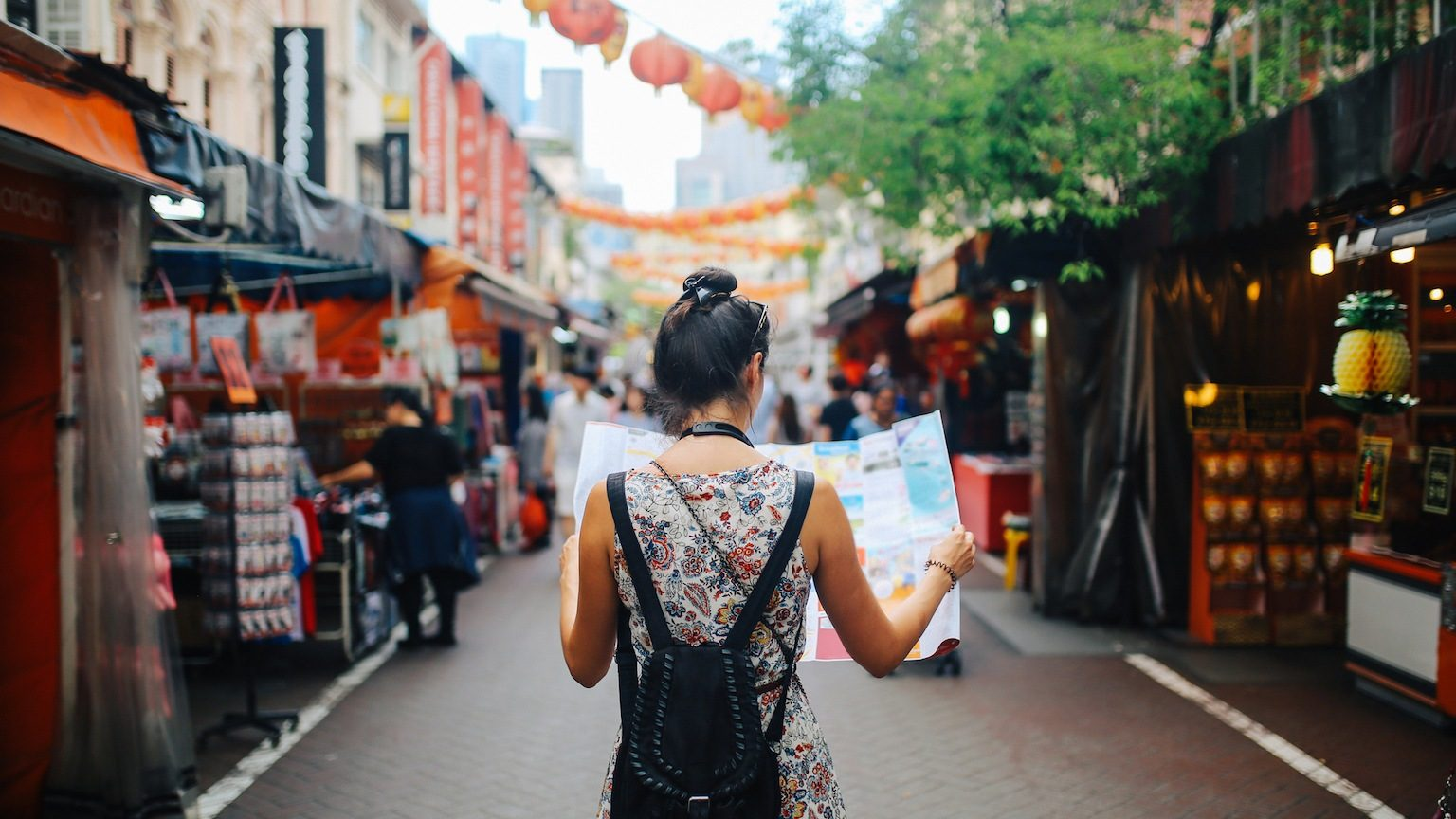 Young traveler woman in Singapore street market checking the map.
