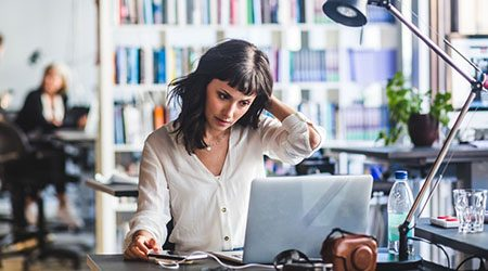 Businesswoman looking at laptop while sitting in office